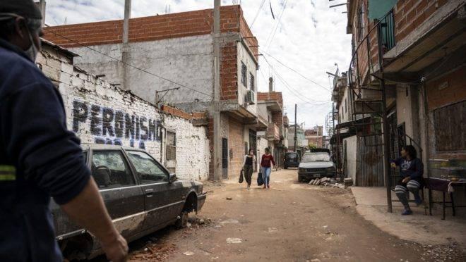 Mulher caminha em favela de Buenos Aires. No Muro, pichação referente ao Peronismo, legado do presidente Juan Perón, morto em 1974.