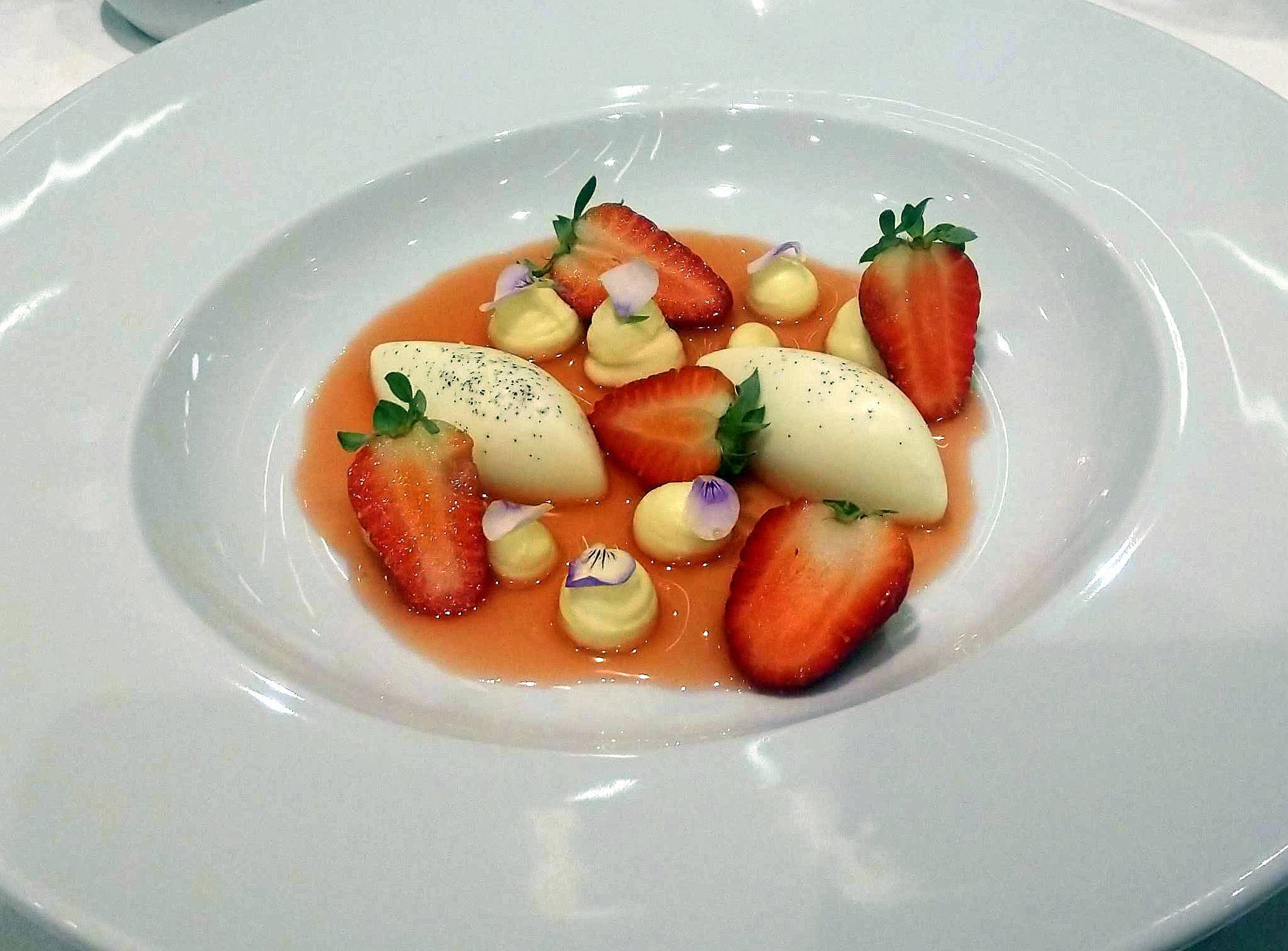 Panna cotta, morangos, calda de morangos e pétalas de amor-perfeito - a sobremesa.