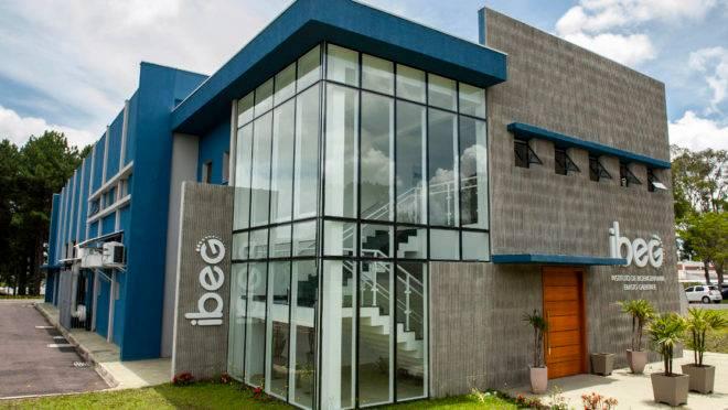 A imagem mostra a sede do Instituto de Bioengenharia Erasto Gaertner (IBEG). É um prédio de dois pavimentosem alvenaria e vidro, nas cores cinza e azul, cercado por um estacionamento.