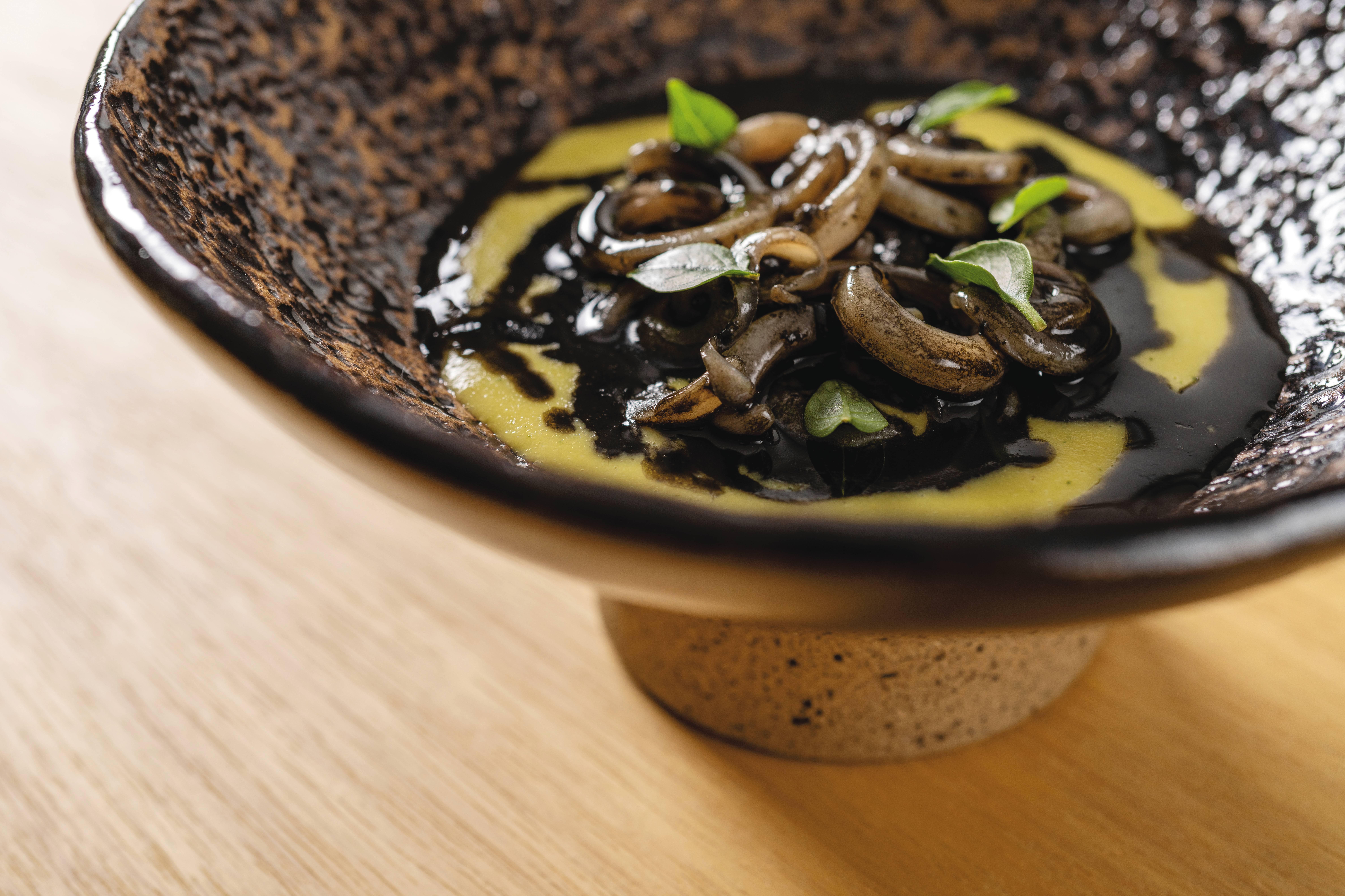 No novo menu, Do Campo ao Mar, combinações surpreendentes como o milho verde assado e cozido com capim-limão, servido com lula e salsa negra de frutos do mar. Foto: Rubens Kato/Manu