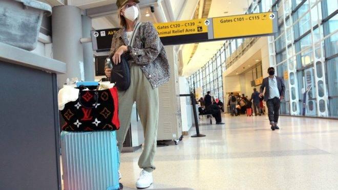De máscara, mulher espera por voo em aeroporto de New Jersey, nos EUA.