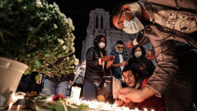 Pessoas fazem homenagens às vítimas de atentado em frente à Basília de Notre-Dame em Nice, França, 29 de outubro