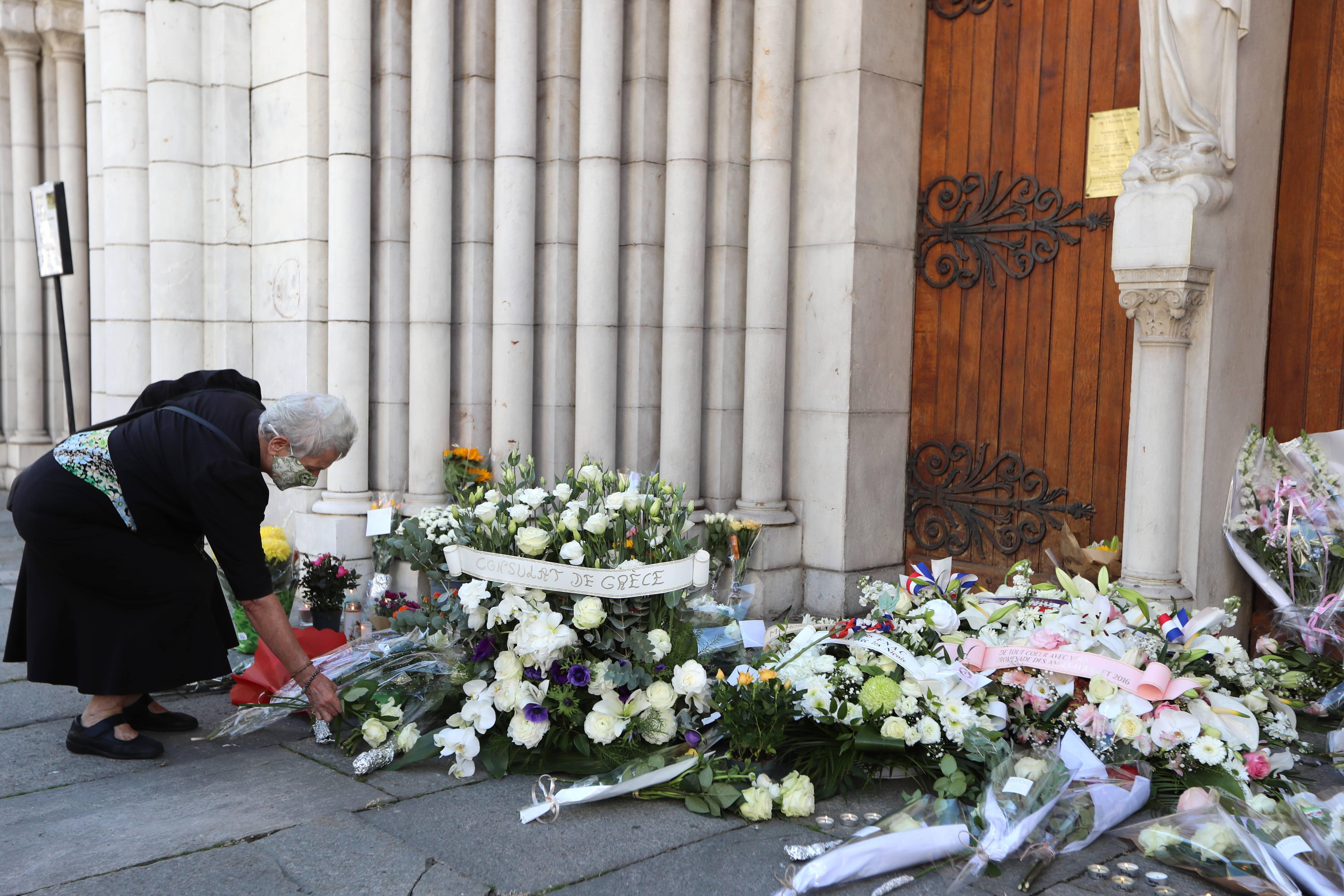 Mulher coloca flores em frente à Basílica de Notre-Dame de l'Assomption em Nice, em 30 de outubro de 2020, durante uma homenagem às vítimas mortas em ataque com faca na igreja, no dia anterior | Foto: Valery HACHE/AFP