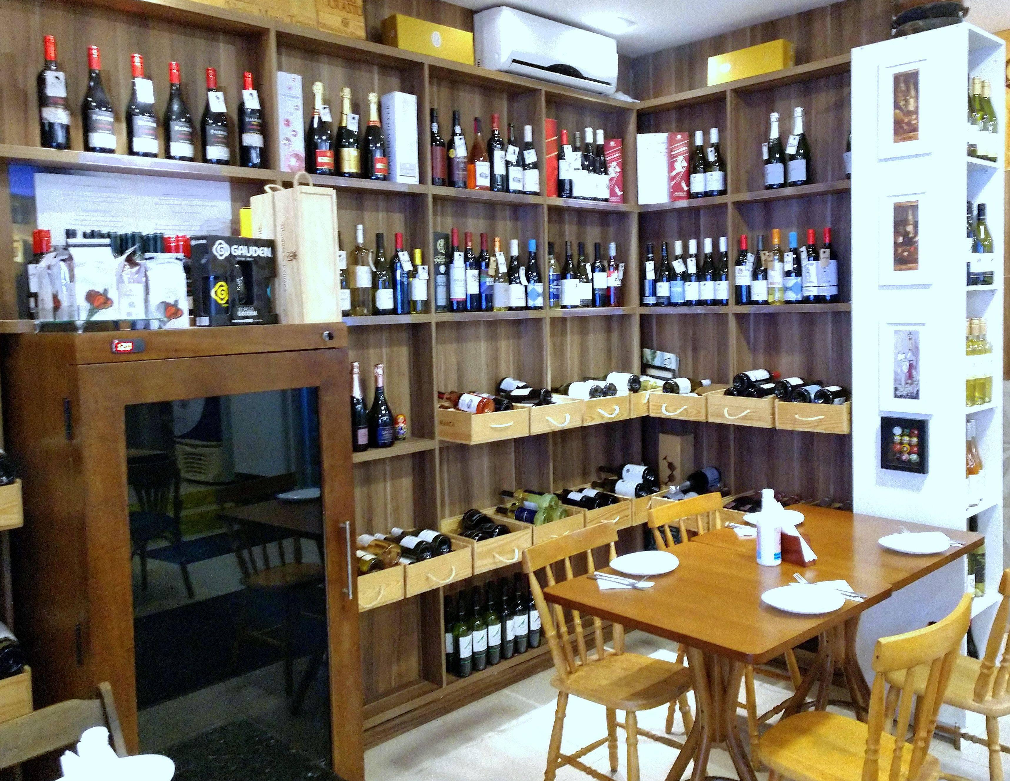 No salão interno, os vinhos fazem parte da decoração da casa.