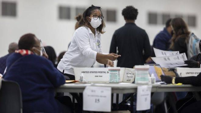 Um trabalhador do Departamento de Eleições de Detroit pede uma cédula por correio no Conselho de Contagem Central no Centro TCF em 4 de novembro de 2020 em Detroit, Michigan.