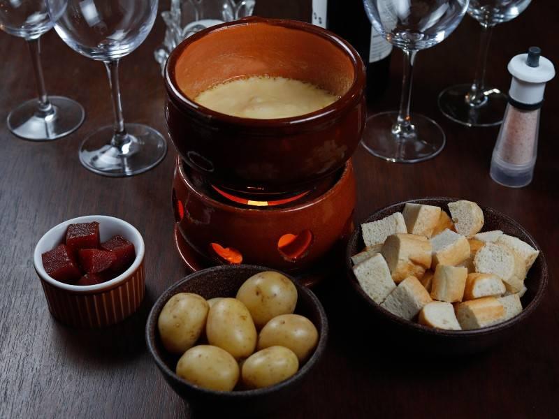 Petit Fondue Suíço, do Château de Gazon, acompanhado de pães, minibatatas e goiabada.