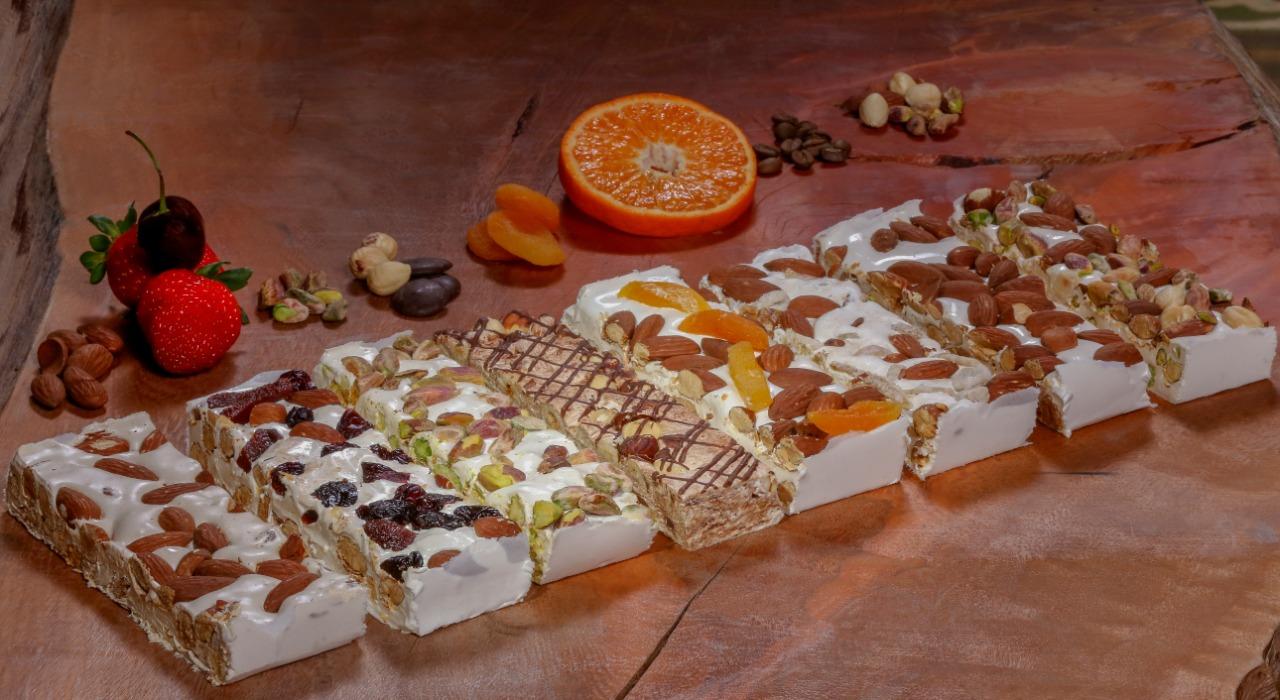 Desde abril os torrones vêm sendo fabricados e testados. Da esquerda para a direita: amêndoas, frutas vermelhas, pistache 100%, chocolate com avelã, damasco, laranja, café e misto.  Três desses já estão à venda.
