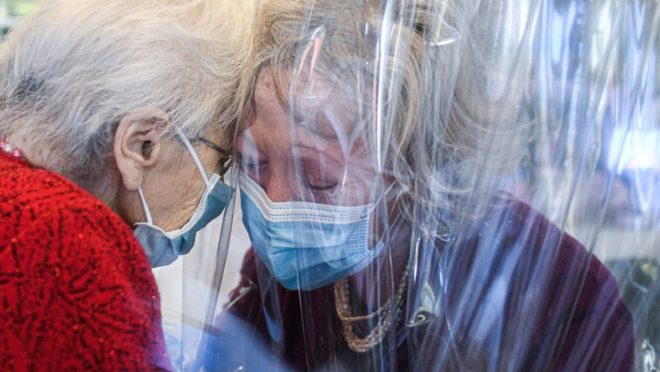 Uma residente da casa de repouso perto de Veneza abraça sua filha, enquanto um plástico separa as duas. me meio à pandemia de coronavírus, em 11 de novembro de 2020, na Itália