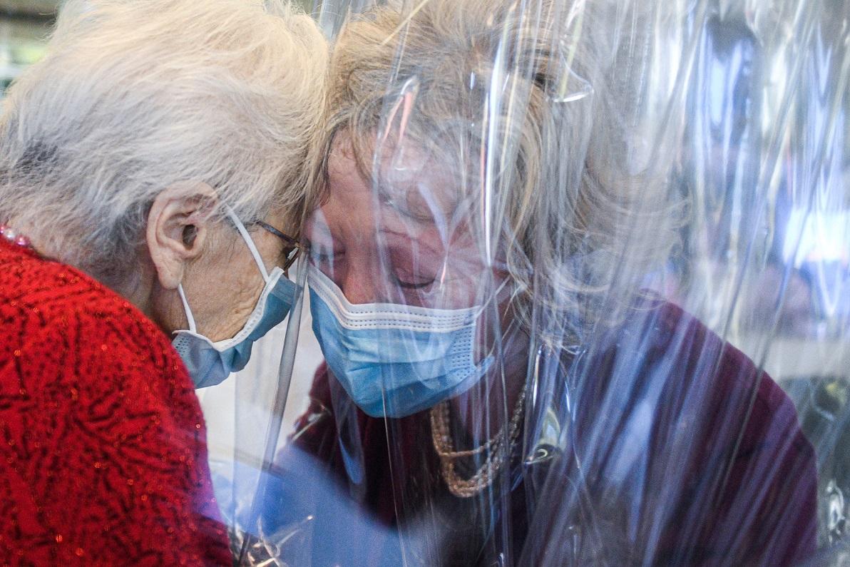 Mãe e filha se abraçam através de um plástico por causa da pandemia de Covid-19, na Itália | Foto: Piero CRUCIATTI/AFP