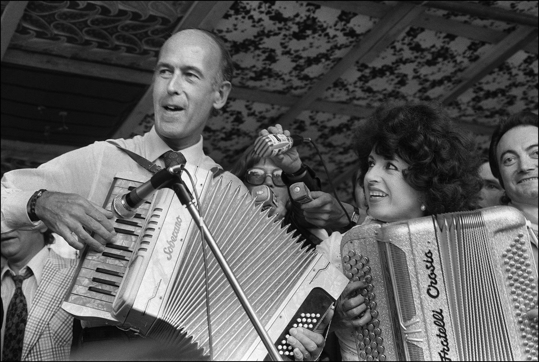 Foto de arquivo tirada em 24 de junho de 1973 mostra o então Ministro das Finanças e candidato à presidência Valery Giscard d'Estaing e a acordeonista Yvette Horner tocando acordeão em Montmorency, durante o segundo festival mundial de acordeão | Foto: DANIEL JANIN/AFP