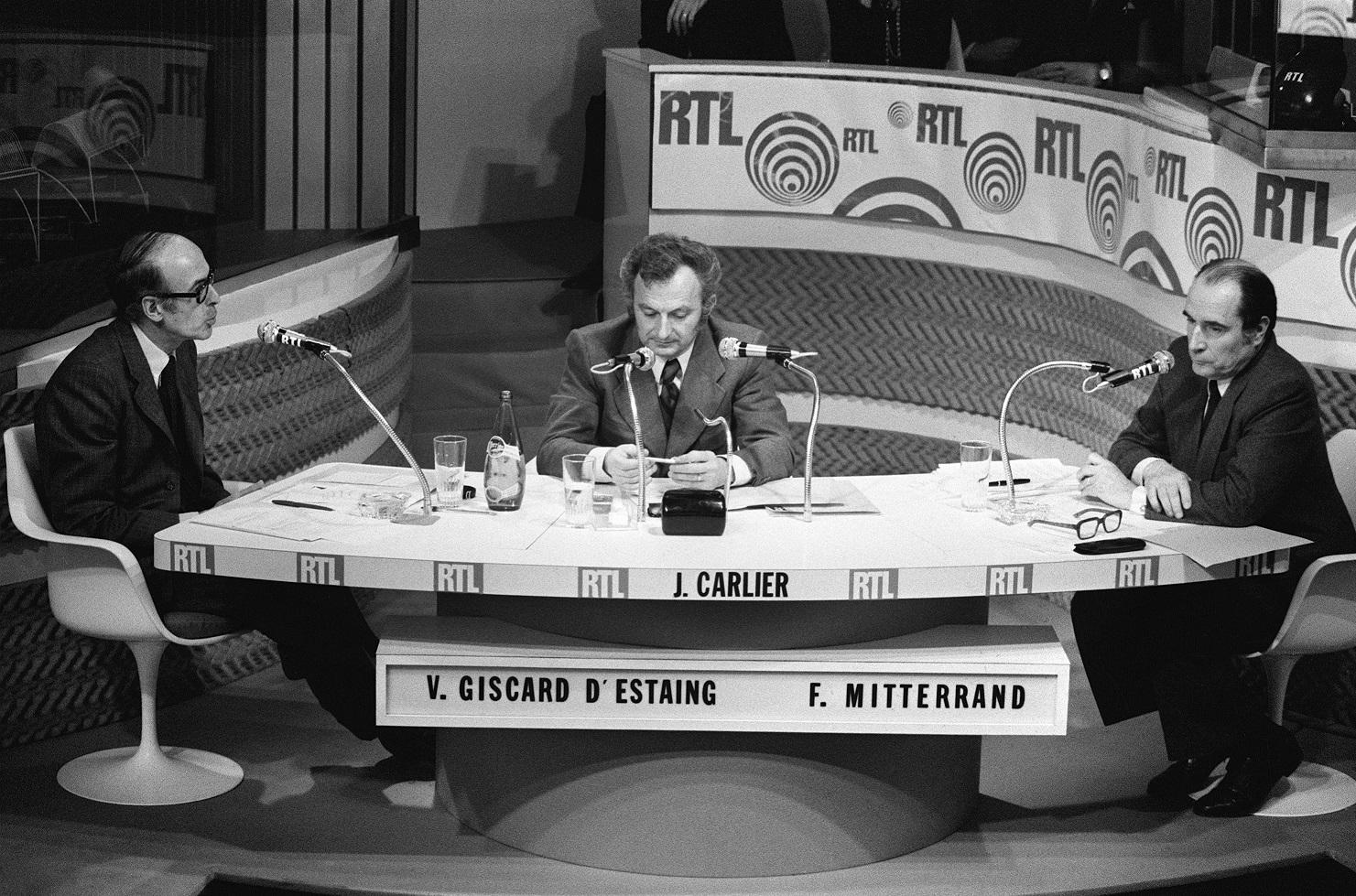 Esta foto de arquivo tirada em 3 de maio de 1974 mostra os então candidatos à eleição presidencial Valery Giscard d'Estaing (E) e François Mitterrand frente a frente no estúdio da rádio RTL, durante um debate com Jean Carlier (C), jornalista da RTL | Foto: AFP