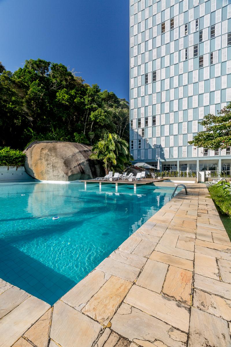A piscina do edifício é integrada às pedras e vegetação do morro vizinho.
