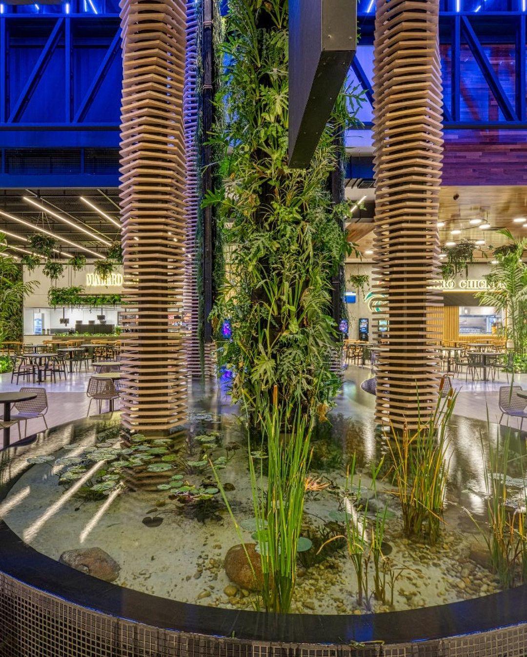Detalhe do hall da EcoParada Madero, com jardim vertical e uma fonte.