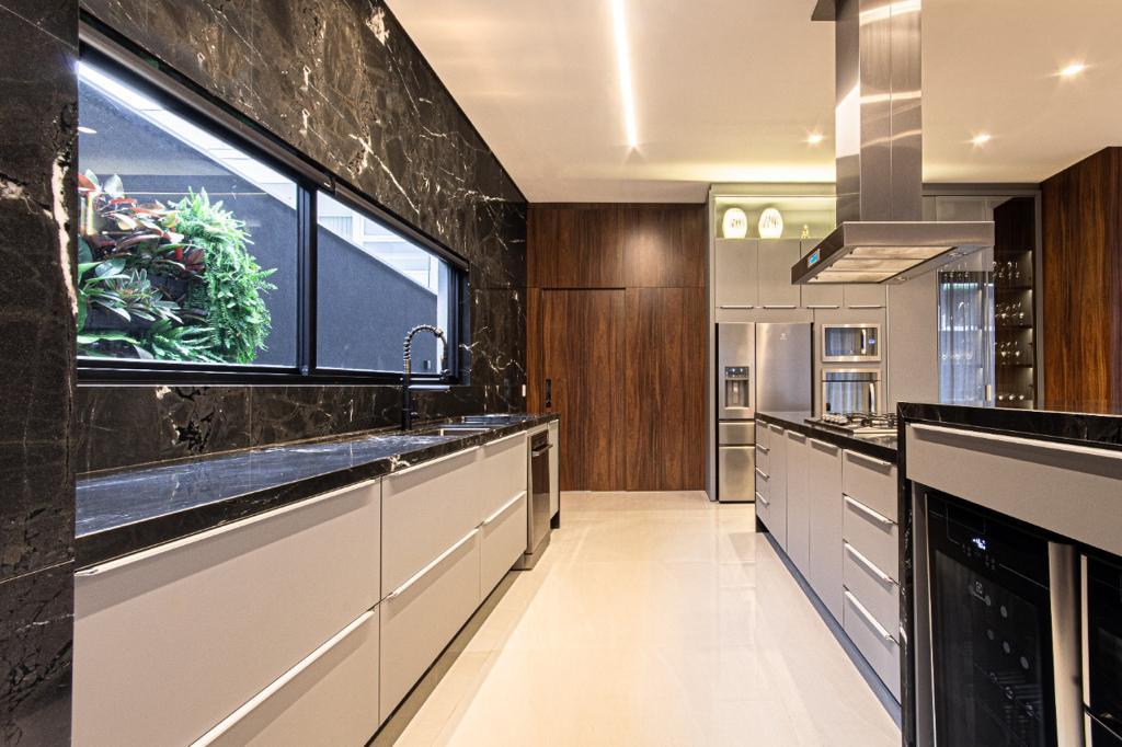 Cozinha do mesmo projeto residencial assinado por Hellen Giacomitti, com destaque para os armários cinzas e a harmonia dos mobiliários com os outros elementos pretos e nudes.