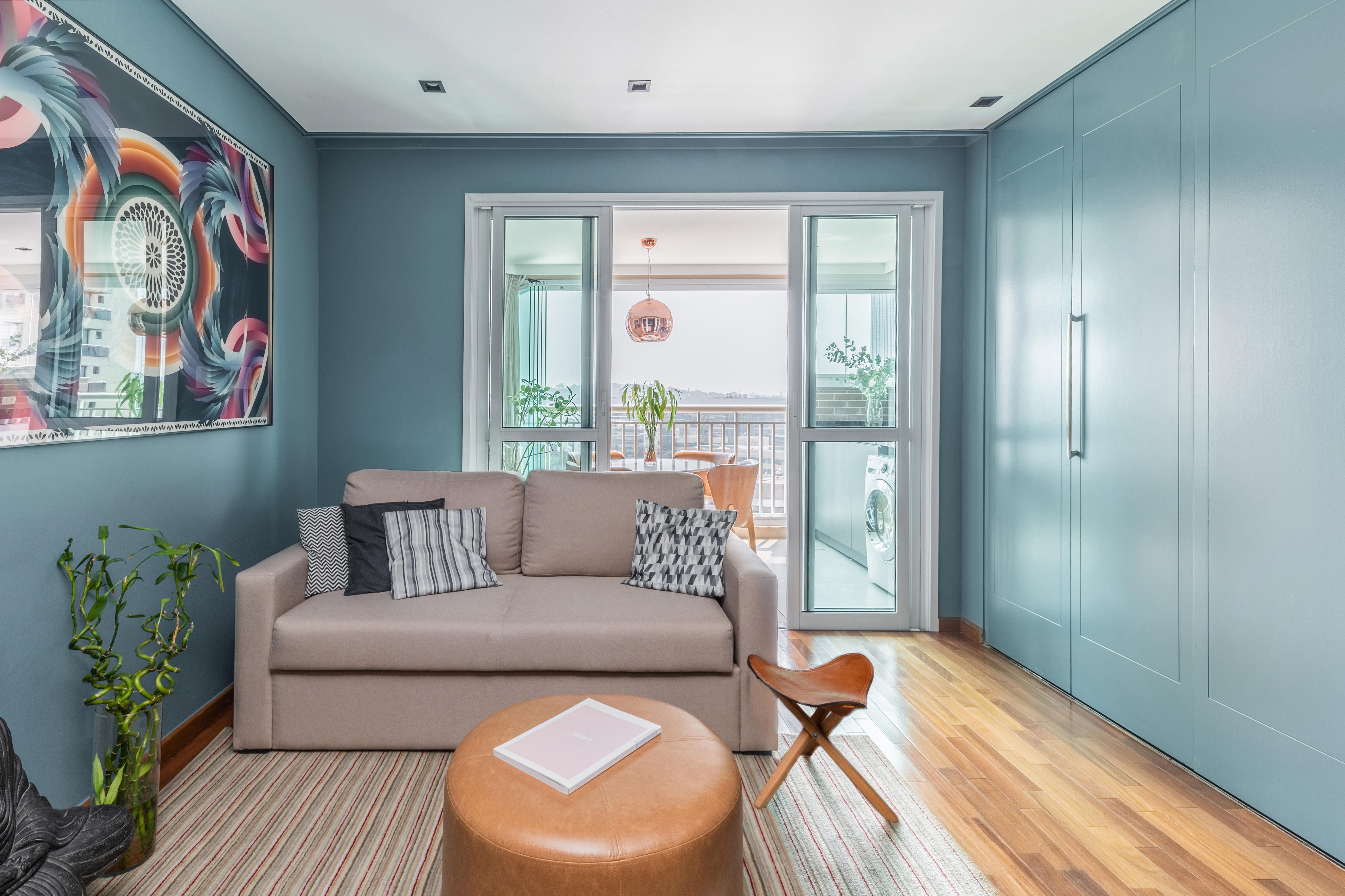 Outro ângulo da sala de estar e TV, que revela a integração com outros ambientes, como a varanda gourmet e a cozinha, que está à direita, com portas fechadas.