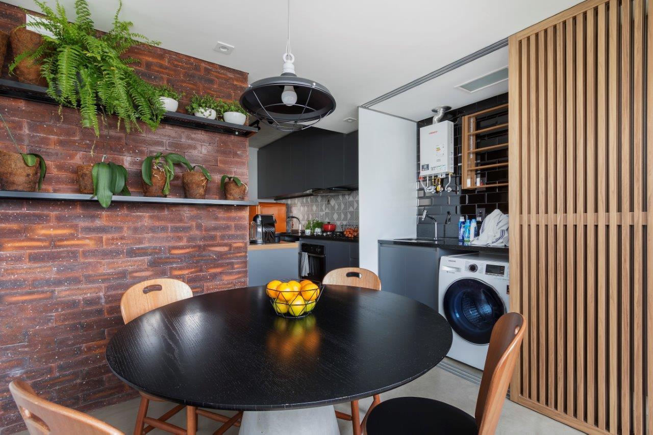 <br />Lavanderia ao lado da cozinha também pode ficar oculta com a marcenaria ripada, que pode ficar aberta ou fechada. Rafael Renzo/Divulgação.
