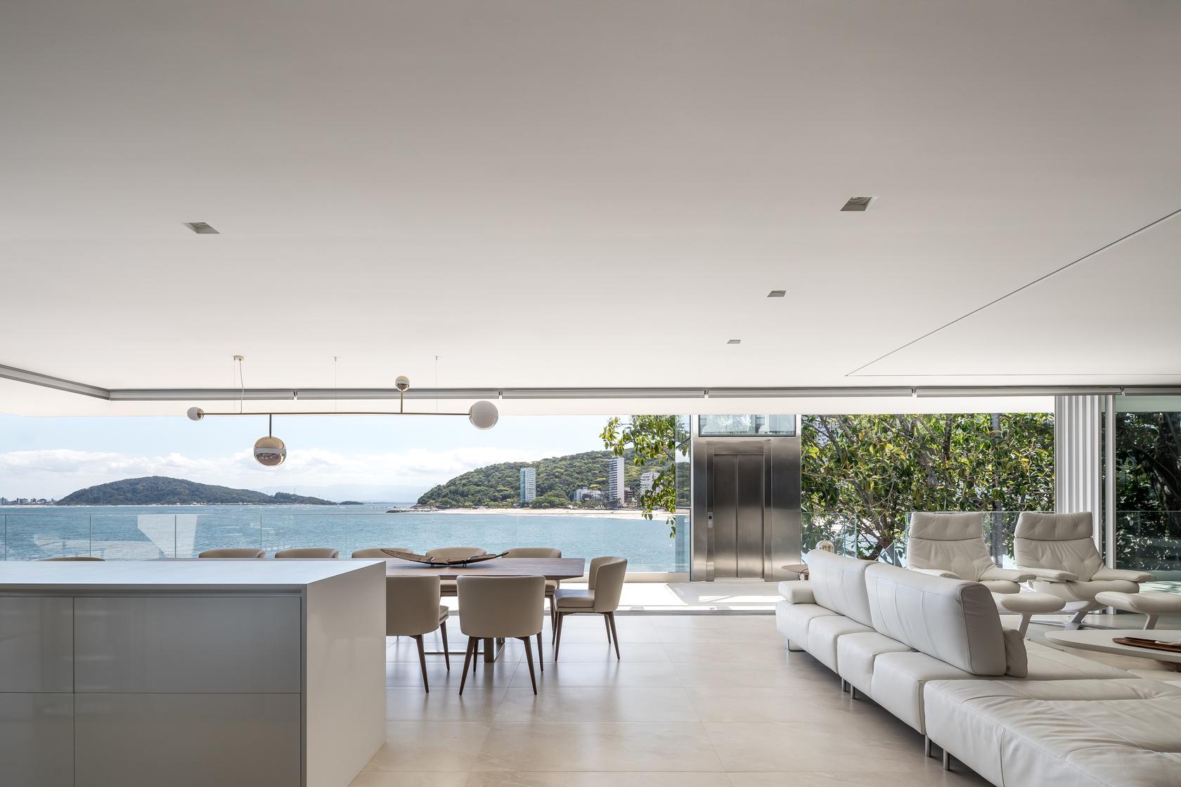 O branco da arquitetura se repete no interior, proporcionando conforto sem interferir na vista.