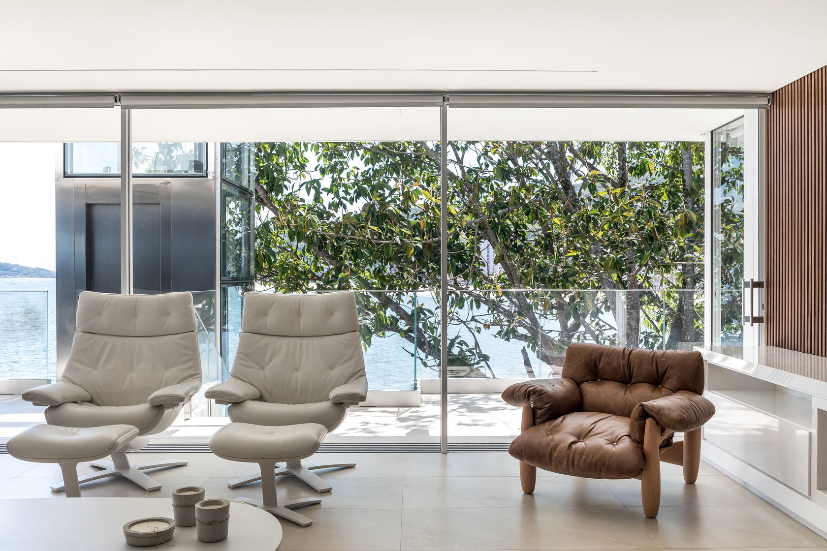 No interior, o estilo minimalista traz móveis em tons neutros, como a poltrona Mole, assinada por Sergio Rodrigues, da década de 1960.