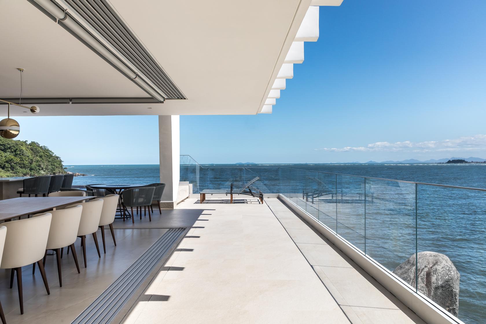 A grande varanda voltada para o mar, que recebeu guarda-corpo em vidro, proporciona momentos de lazer para a família e seus convidados.