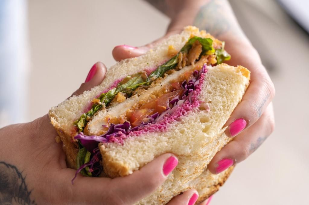 frango no pão brioche com húmus de beterraba, salada de repolho e molho especial. Foto: Divulgação/Manuzita