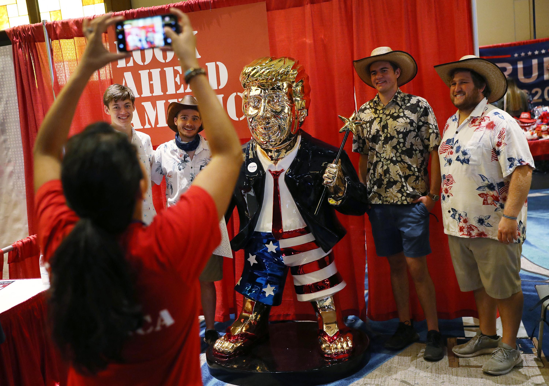 Apoiadores de Trump tiram foto com a estátua do ex-presidente na Conferência de Ação Política Conservadora   Foto: Joe Raedle/Getty Images/AFP