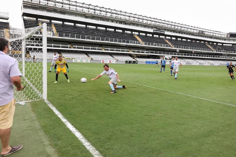 Bolsonaro faz gol em jogo beneficente em Santos junto com amigos. O goleiro está como a oposição, inerte.