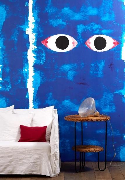 Um dos papéis de parede que Paola Navone assina para NLXL, com tons de azul forte e olhos como os olhos de Buda, bem tradicionais no Sudeste Asiático.