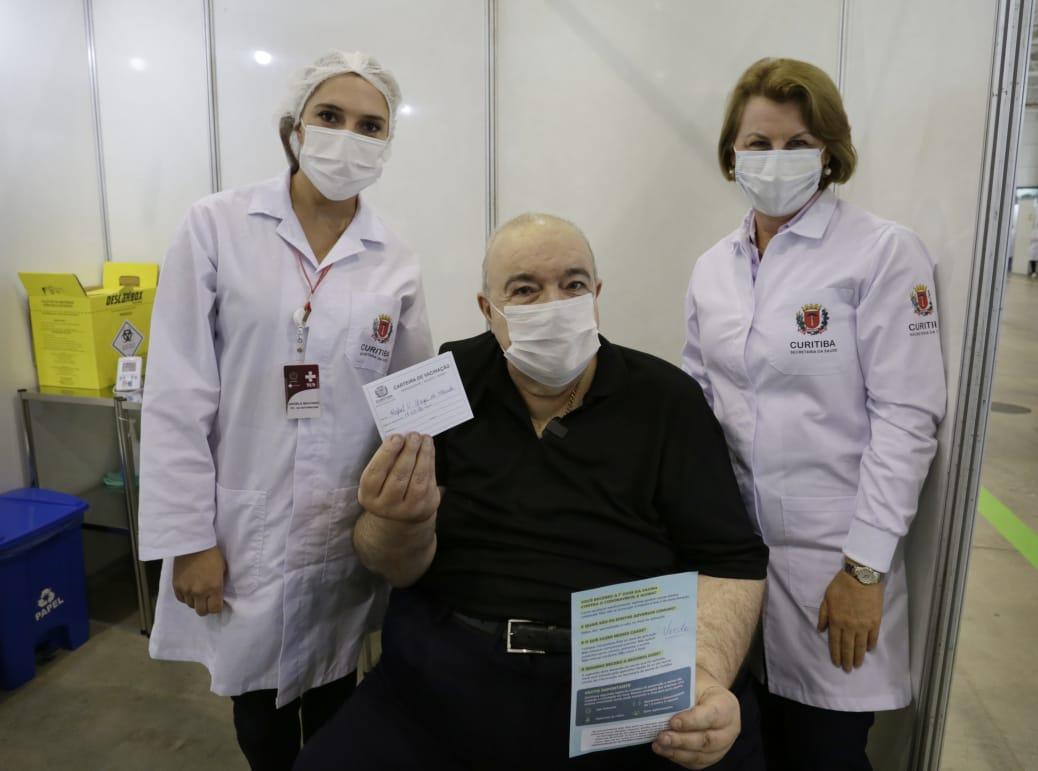 O prefeito de Curitiba, Rafael Greca, mostra o comprovante de vacinação ao lado da técnica de enfermagem Ângela Cristina Machado e da secretária municipal de Saúde, Márcia Huçulak. Foto: Ricardo Marajó