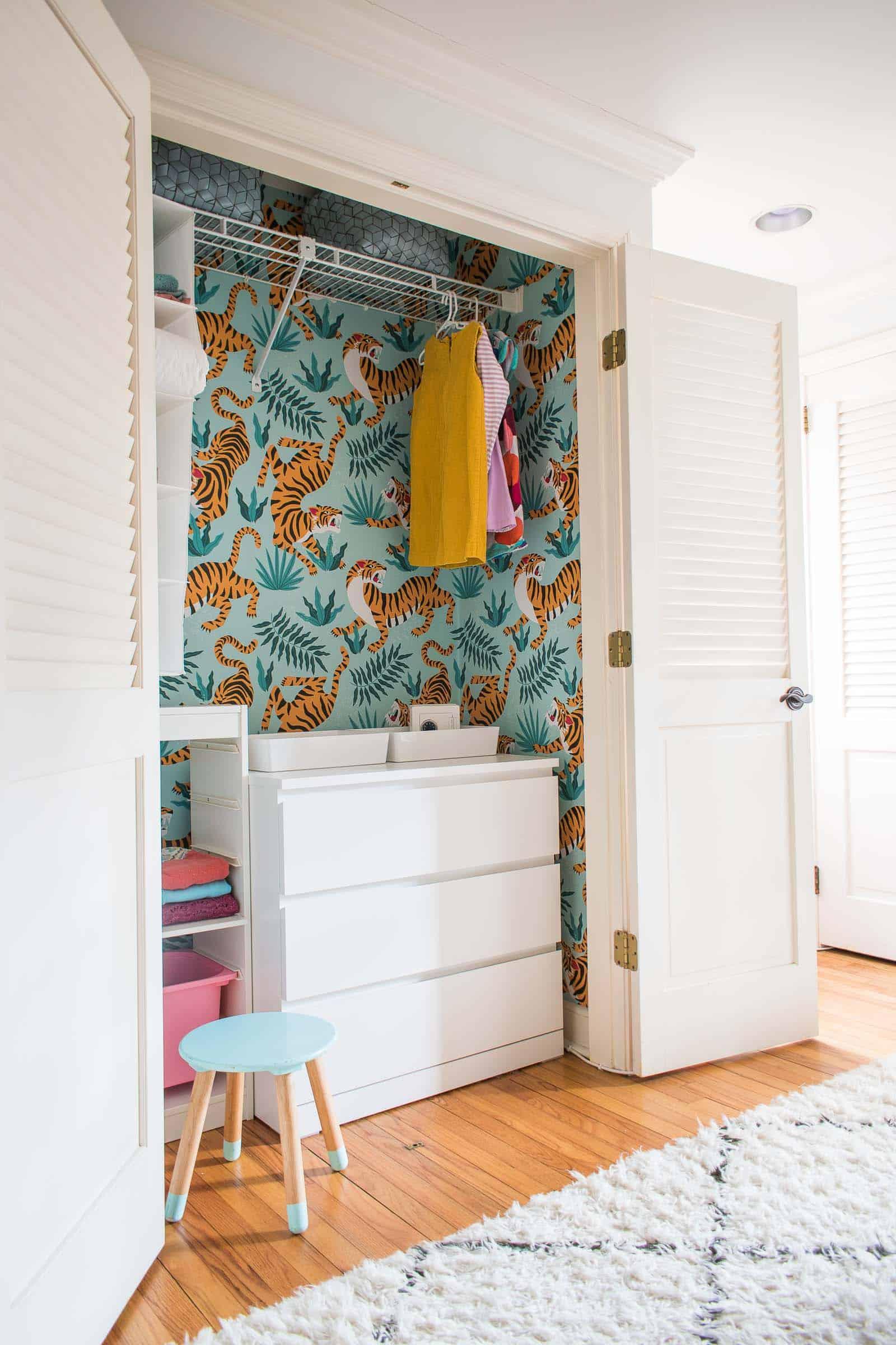 """Armário dos filhos é transformado pela blogueira Charlotte Smith, do portal """"At Charlotte's House"""", com papel de parede verde com folhagens e tigres."""