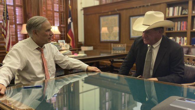Gov. do Texas Greg Abbott (esq.) conversa com o xerife de Jackson County.