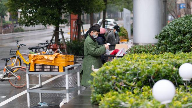 Pessoas com máscaras vendem comida durante o lockdown em Wuhan China no dia 24 de janeiro de 2020. Imagem ilustrativa.