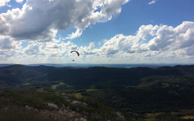 Imagem do cume do Morro do Cal. Céu azul com nuvens brancas e uma pessoa, ao longe, voando de parapente.
