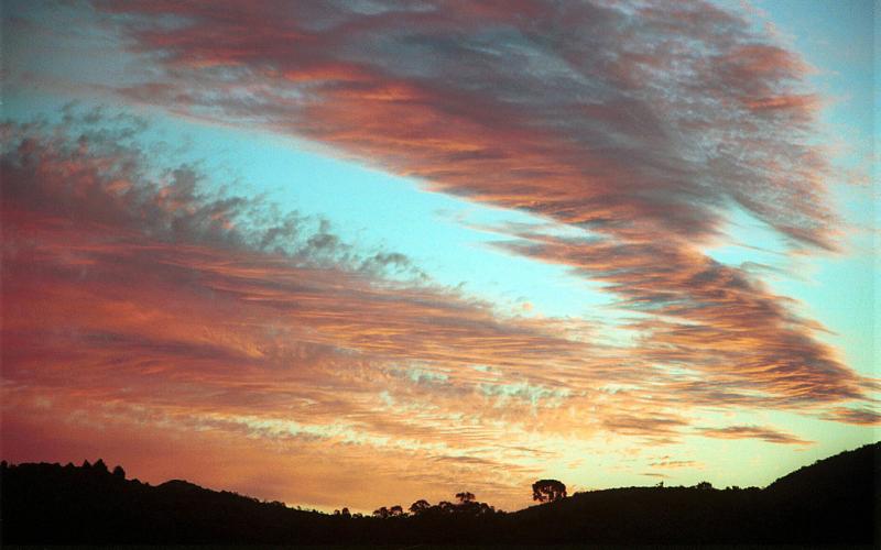 Morro da Palha. Vista do céu em fim de tarde, com as cores azul, laranja e rosa nas nuvens.