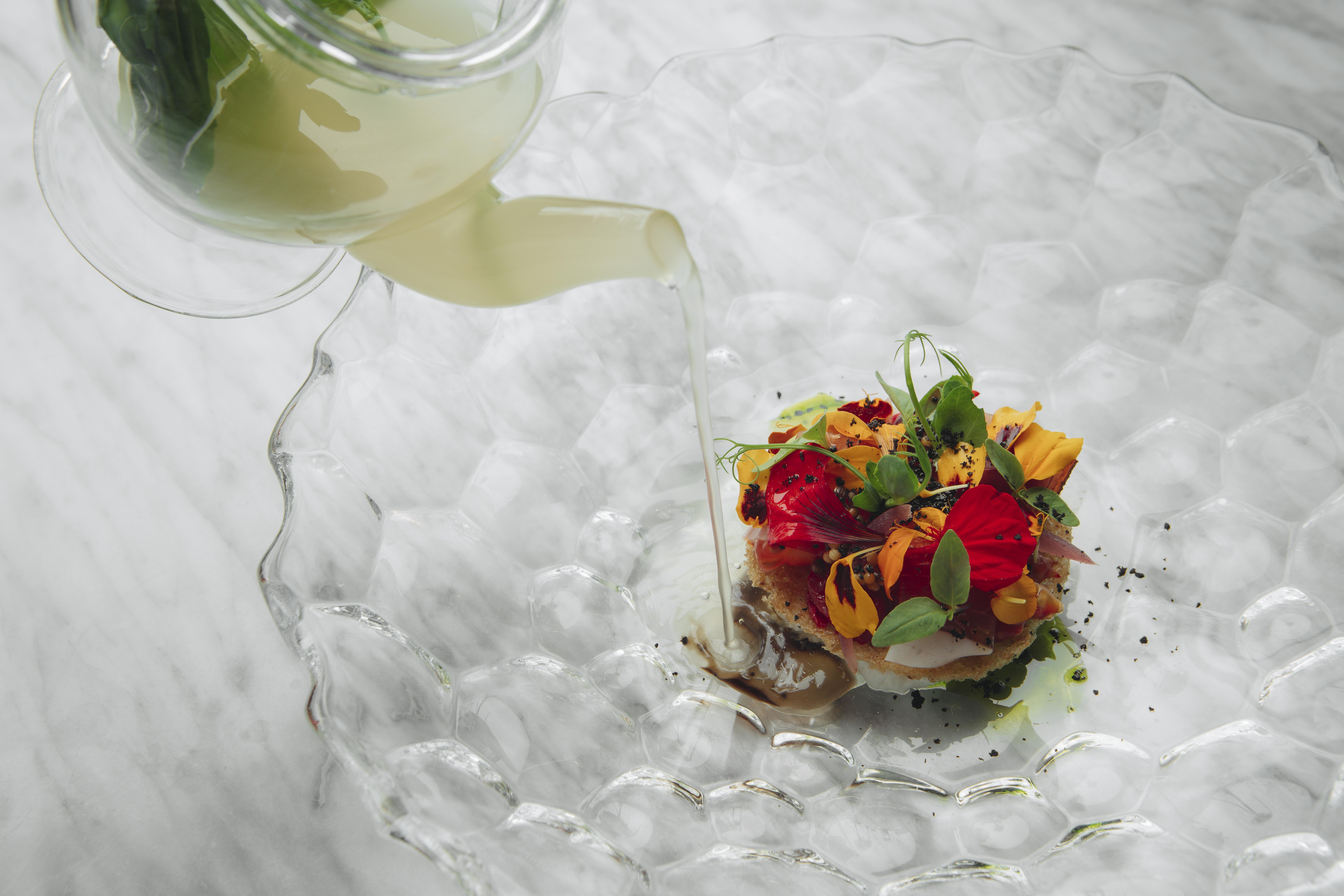 Água clara de tomate para a salada com pão velho, azeitona, manjericão e flores.