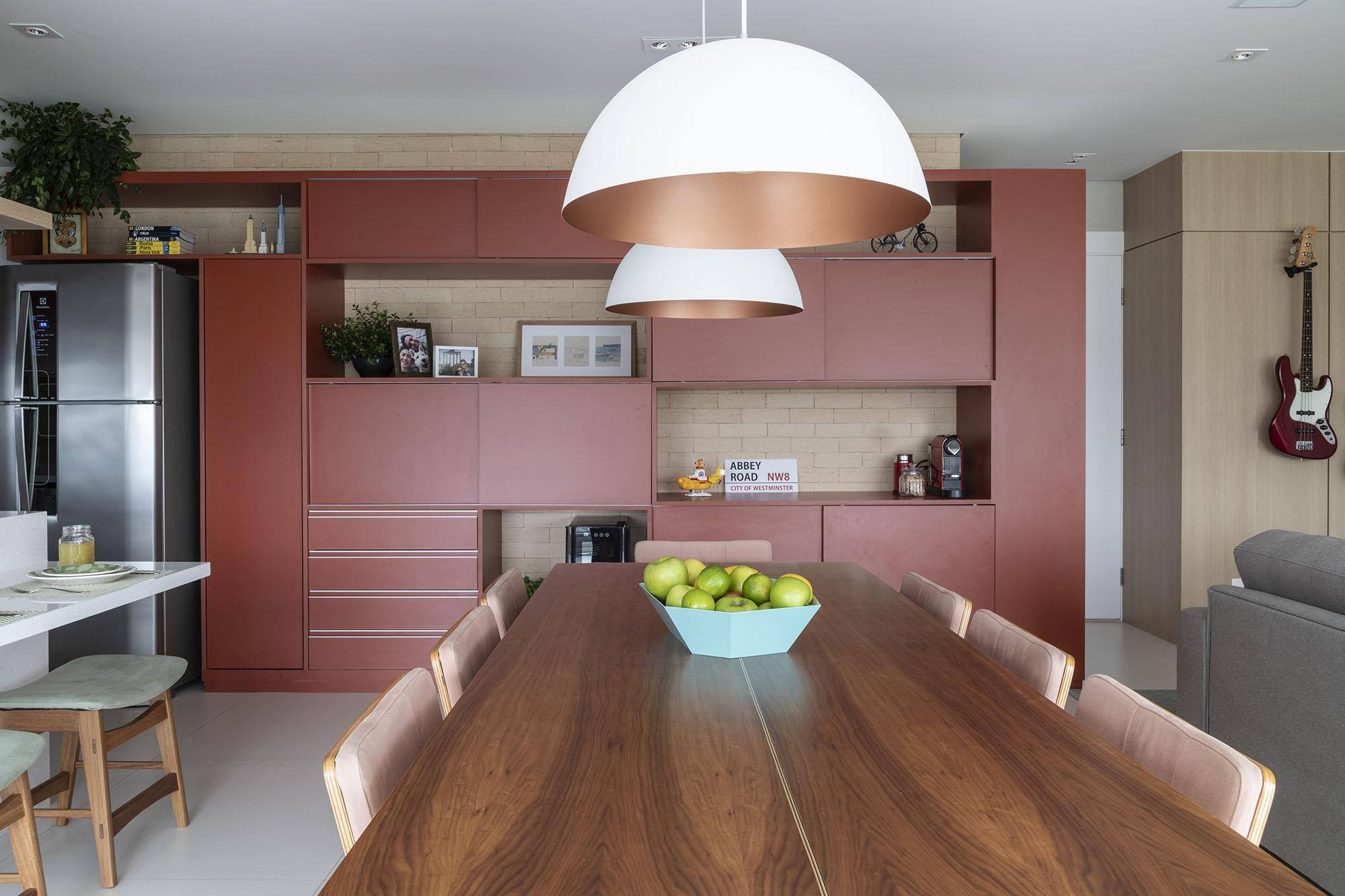 Armário desenhado pela arquiteta é a estrela da área social, que integra cozinha, sala de jantar, churrasqueira e sala de estar.