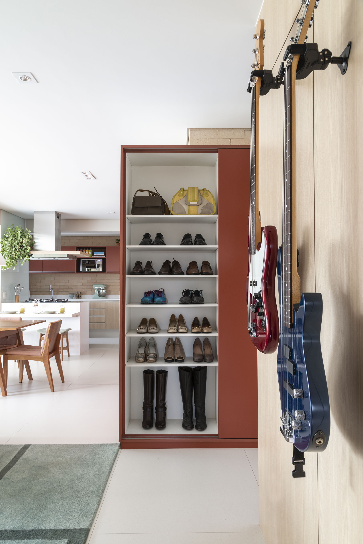 """Como os moradores não gostam de entrar no apartamento usando calçados, sapateira """"secreta"""" foi estrategicamente posicionada na entrada da área social."""