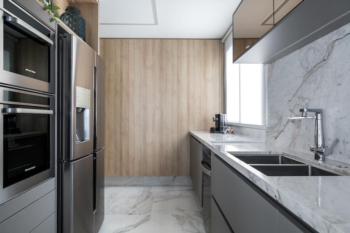 Cozinha projetada por Alessandra Gandolfi é revestida em Mármore Branco Paraná.