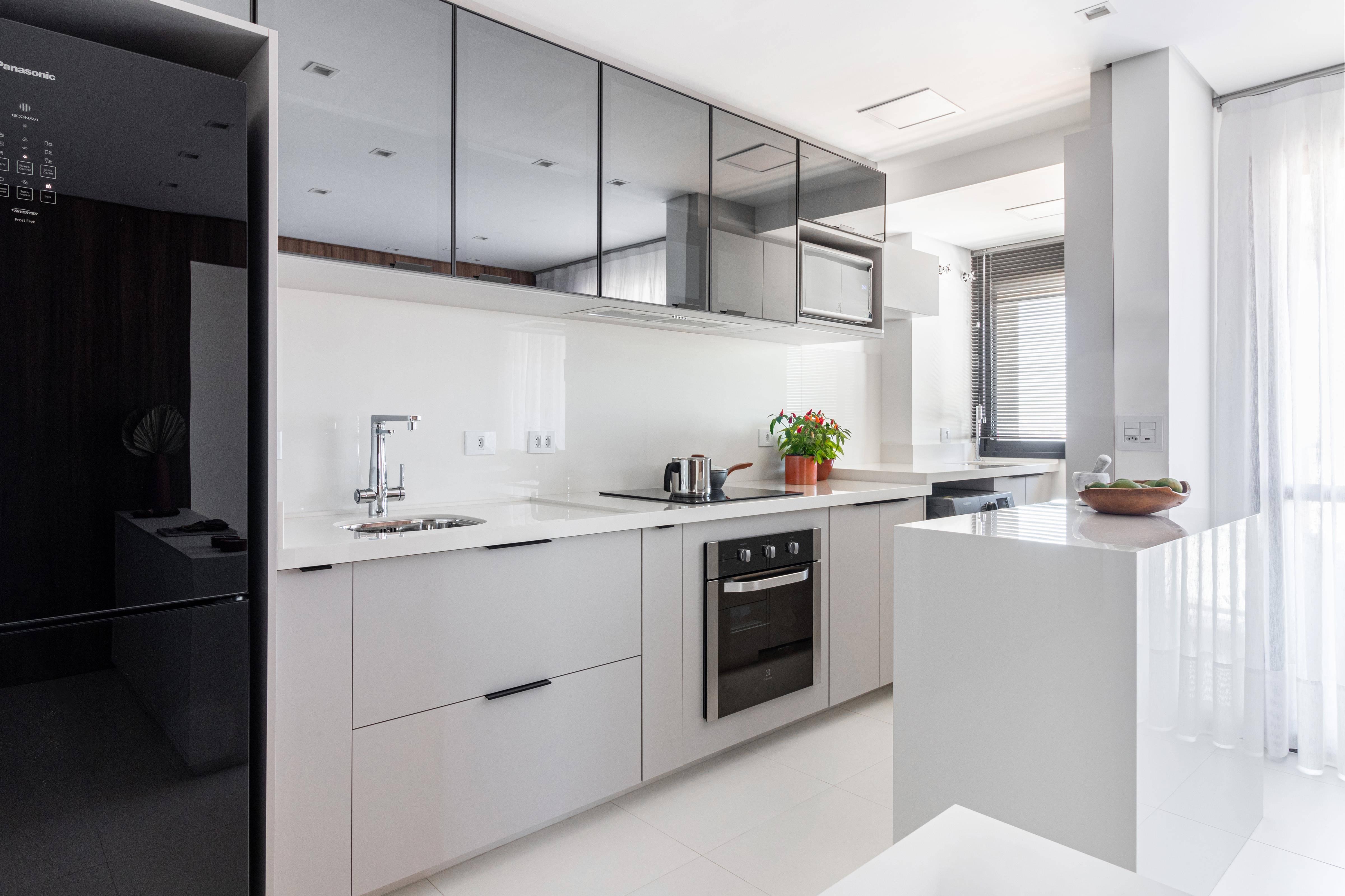 Na cozinha assinada por Julia Lis, a arquiteta optou por vidro reflecta fumê e pedra com acabamento brilhante para garantir uma essência sóbria e elegante.