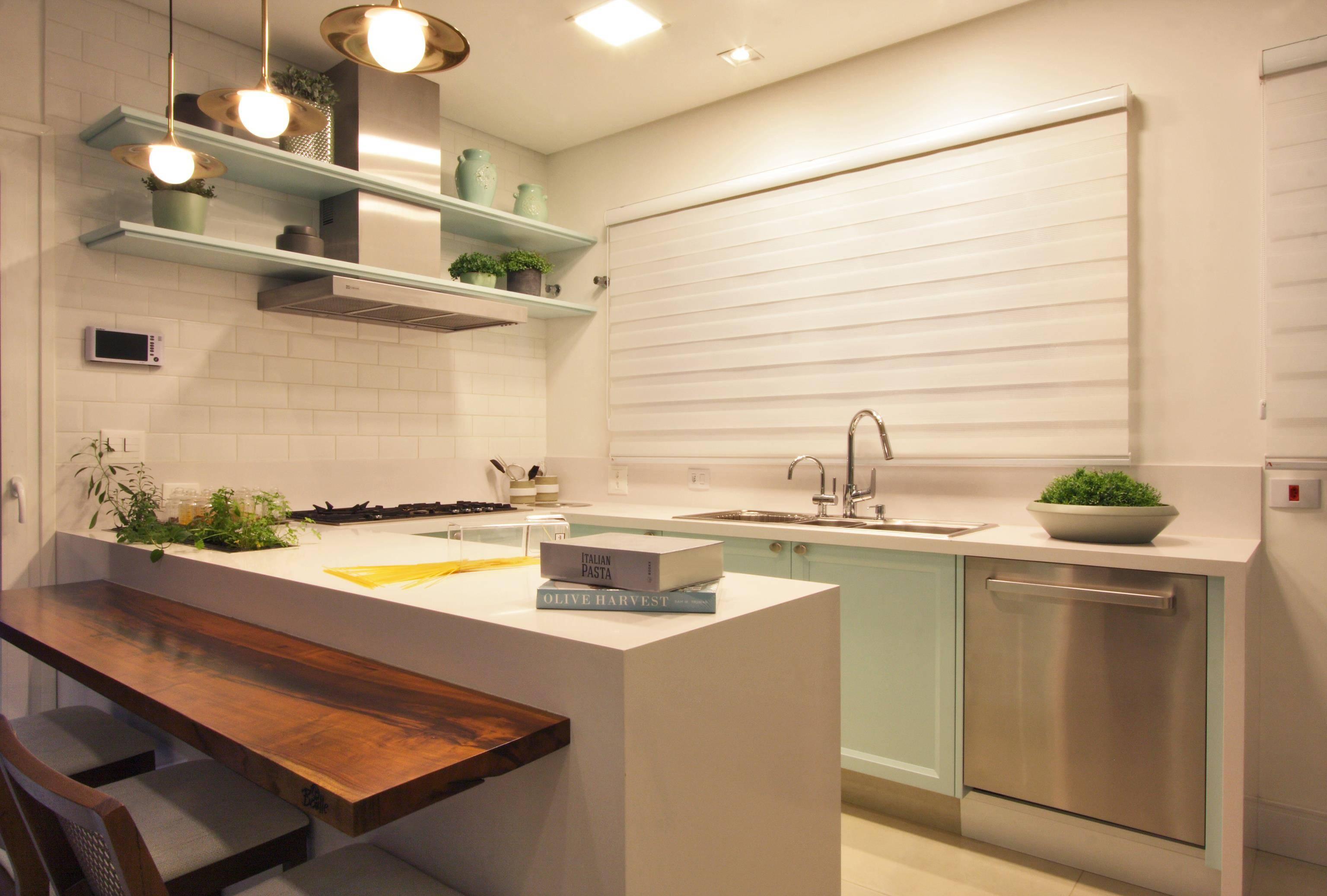 Cozinha projetada por Laryssa Rocha recebeu bancada de pedra Silestone branca, com parte em madeira, que serve tanto para dividir os ambientes, como para refeições rápidas.