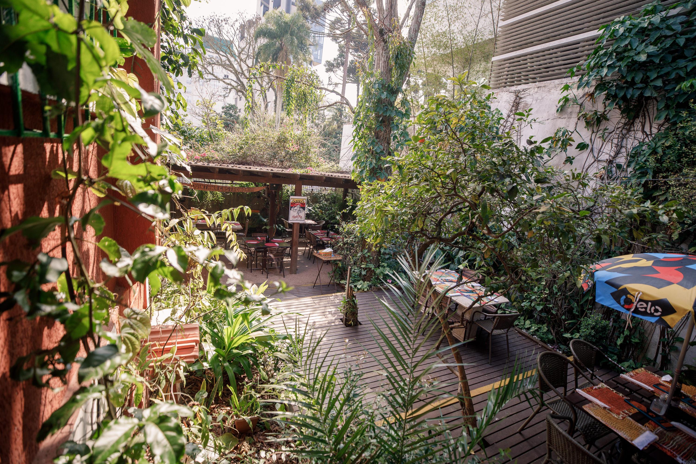 O jardim encantado do Quintana, com mesas entre árvores, arbustos, ervas, frutíferas e colmeias.