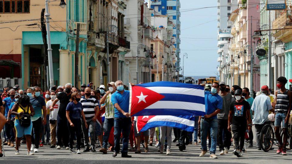 """Centenas de cubanos saíram às ruas de Havana gritando """"liberdade"""" em manifestações pacíficas, que foram interceptadas pelas forças de segurança e brigadas de apoiadores do governo, resultando em violentos confrontos e prisões."""