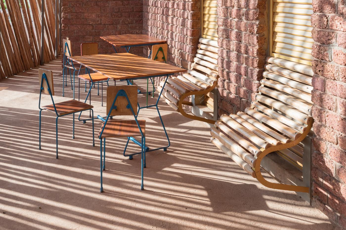 Detalhe das mesas e cadeiras criadas com materiais da região, e dos bancos de madeira que surgem das janelas.