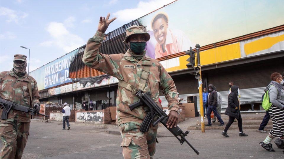 Soldados da Força de Defesa da África do Sul patrulham as ruas enquanto residentes fazem a limpeza de negócios locais que foram saqueados nos tumultos em Joanesburgo, 15 de julho