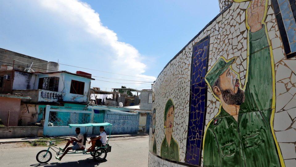 Um bicitaxi passa em frente a um mural com ilustração do ditador Fidel Castro em Havana, Cuba, 13 de agosto