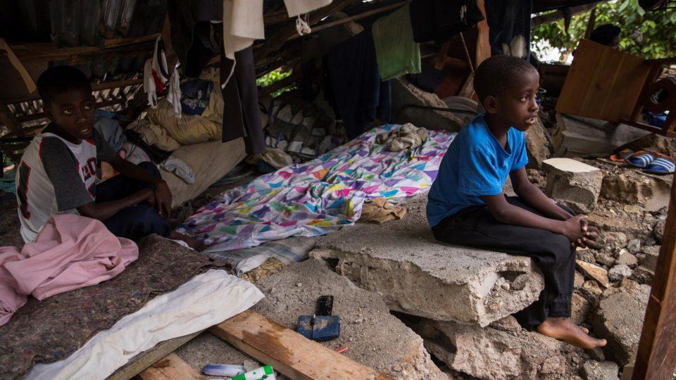 Crianças permanecem protegidas nos restos de sua casa enquanto são registradas chuvas da tempestade Grace em Camp Perrin, Haiti, 17 de agosto