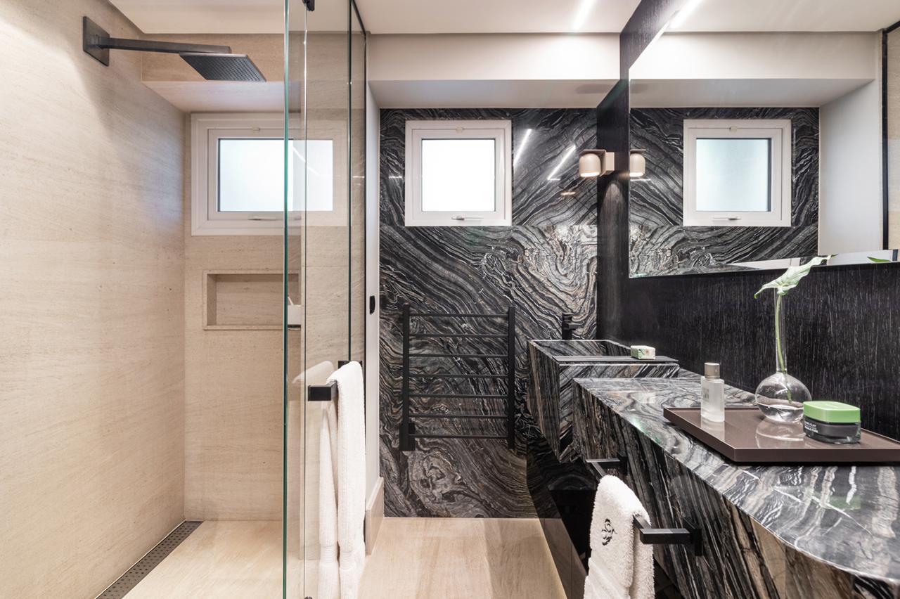 Até mesmo no acabamento do banheiro da suíte, o contraste entre preto e branco nas pedras naturais.