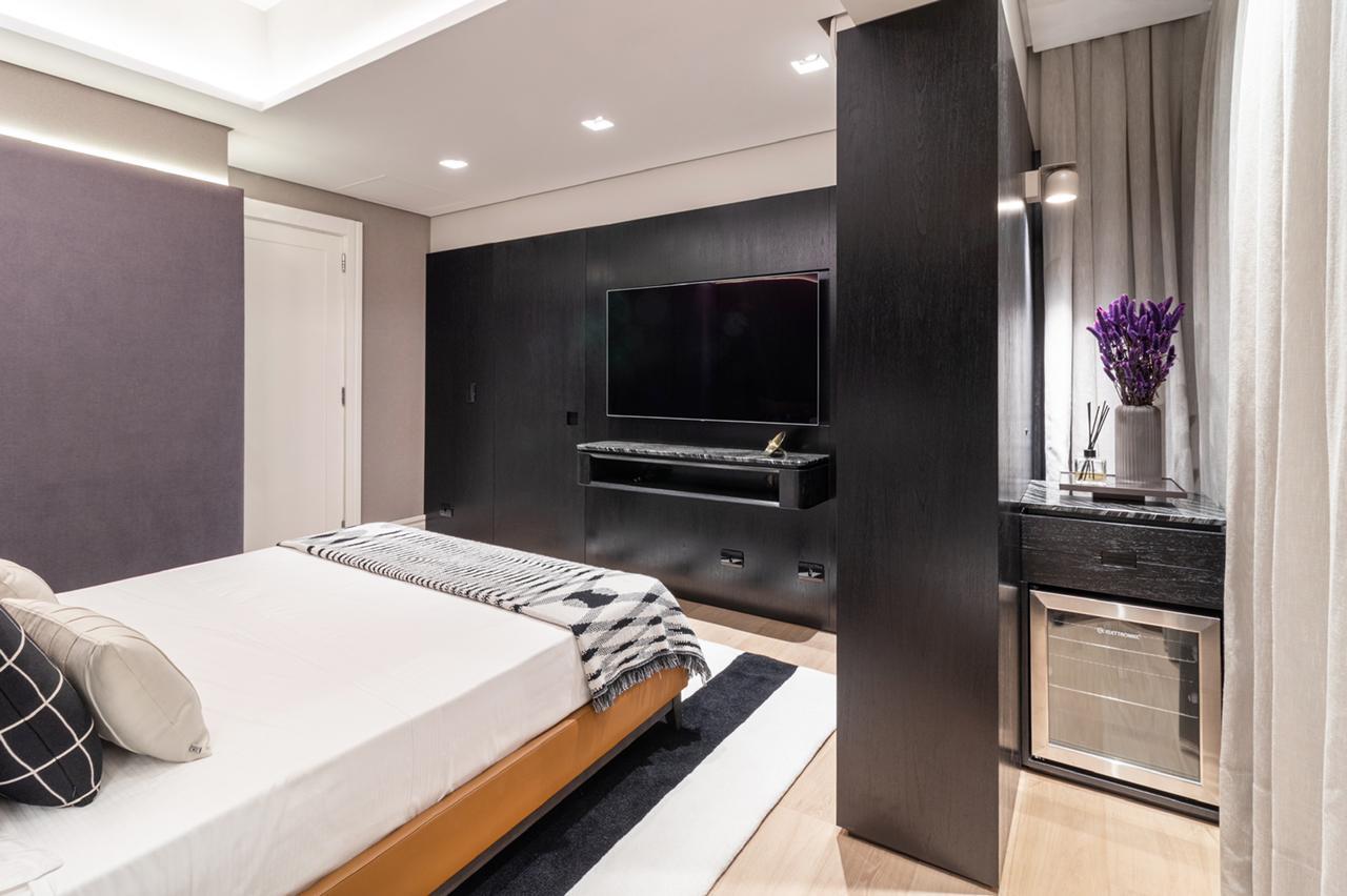 Na suíte mais escura, diversos móveis pretos completam a decoração.
