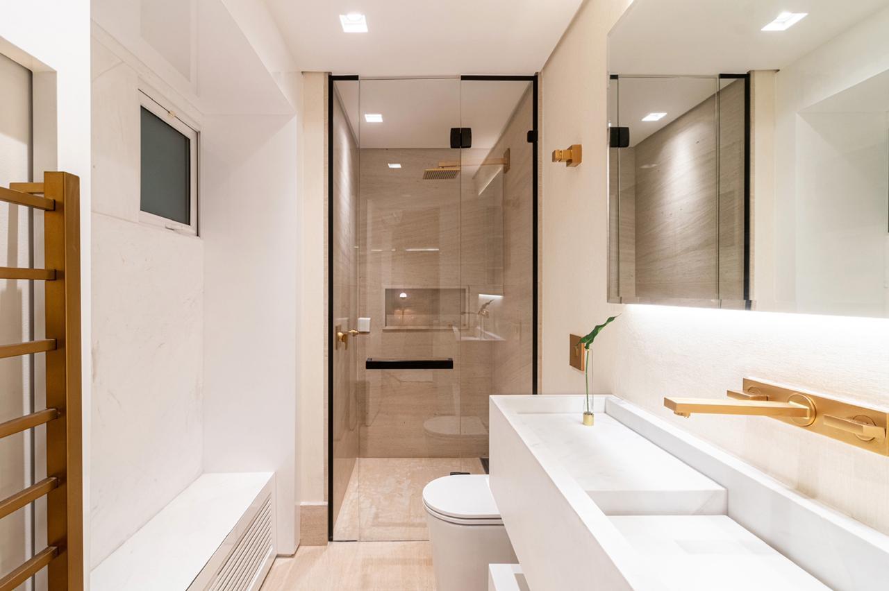 No banheiro da suíte branca, metais em dourado fosco.
