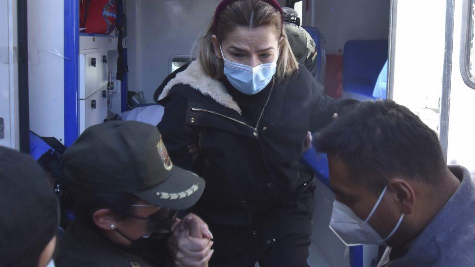A ex-presidente interina da Bolívia Jeanine Áñez é assistida por policiais ao voltar para a cadeia após ser atendida em um hospital