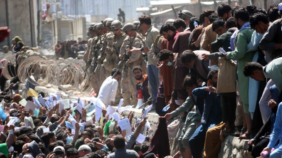 Vários afegãos mostram credenciais a forças internacionais para tentar fugir do país em um dos voos da operação de evacuação, no Aeroporto Hamid Karzai, Cabul, Afeganistão, 26 de agosto